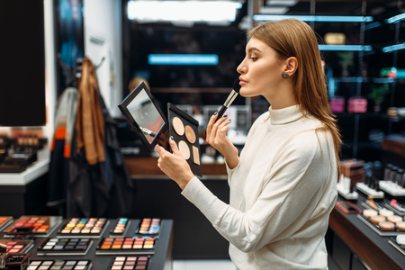 Female customer looks at the mirror in makeup shop Banque d'images