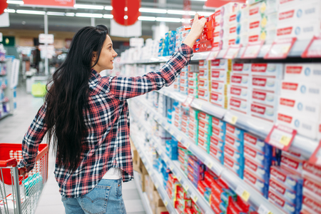 Young woman buying toothpaste in supermarket
