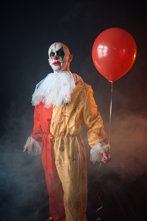 Bloody clown in carnival costume holds air balloon Standard-Bild