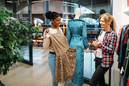 Two female friends choosing dresses, shopping Reklamní fotografie