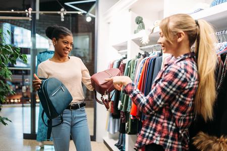 Two females choosing bags in shop, shopping
