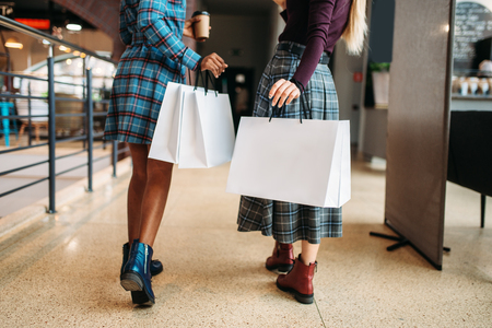 Two female persons with shopping bags in shop