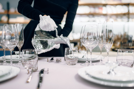 La cameriera versa le bevande nei bicchieri, apparecchiando la tavola Archivio Fotografico