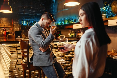 Man lovingly looks on woman at wooden bar counter Stockfoto