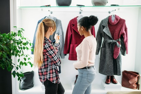 Two girlfriends looking at coat in shop, shopping Stock Photo
