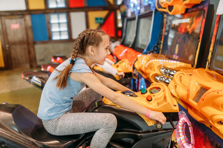 Two girls plays game machine, entertainment center