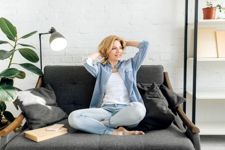 Young woman with book stretch out on cozy couch Stock Photo