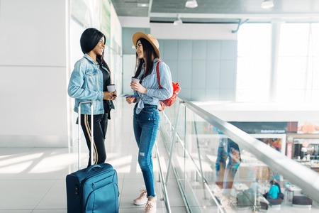 Two female travelers with luggage in airport Stock Photo