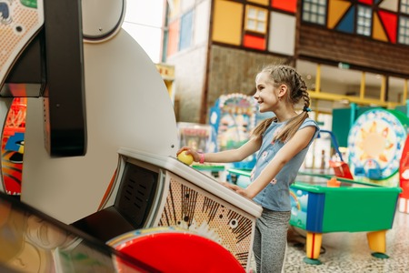 Little girl plays on video game machine