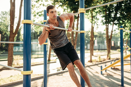 Man doing exercise on horizontal bar outdoor