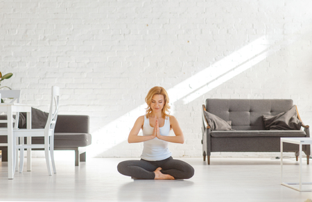 Yuong woman sitting on the floor in yoga pose Stockfoto