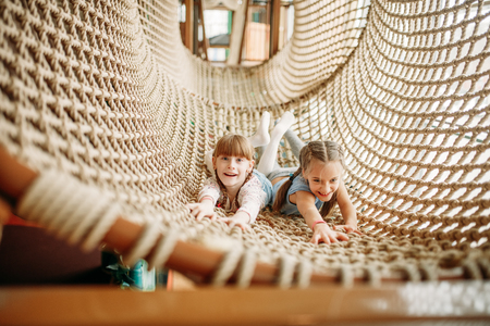 Two girls poses in rope net, children game center