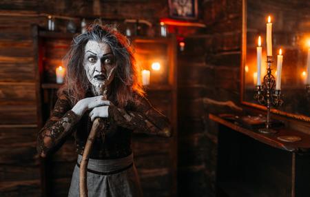 Bruja aterradora con un bastón en el espejo y velas. Foto de archivo