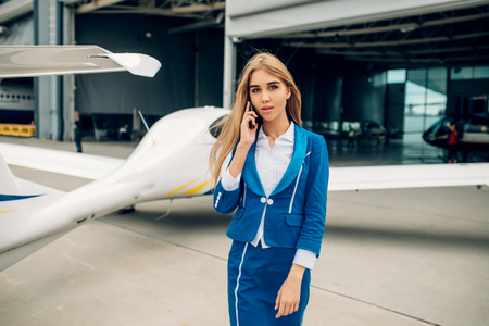 Stewardess in uniform poses against small airplane
