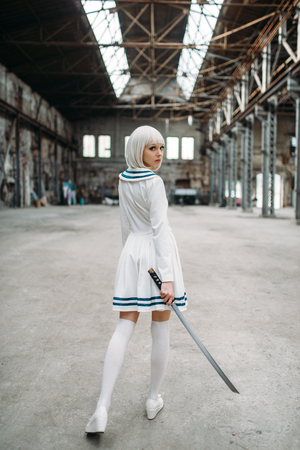 Sexy anime style blonde woman with sword, back view. Cosplay fashion, japanese culture, doll with blade on abandoned factory