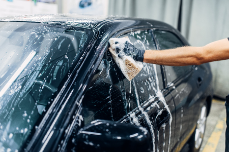 Carwash service, car cleaning, front view. Auto detailing, worker soaps glasses Stok Fotoğraf