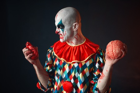 Mad bloody clown holds human heart and brain