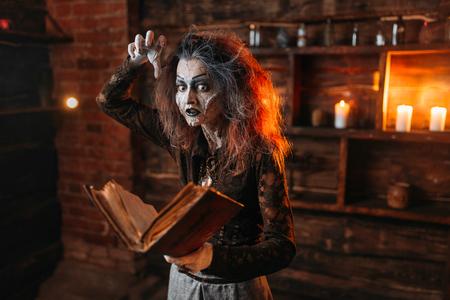 Witch holds spellbook, dark powers of witchcraft