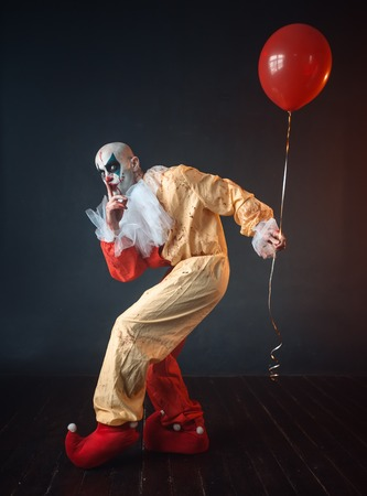 Bloody clown in carnival costume holds air balloon 스톡 콘텐츠