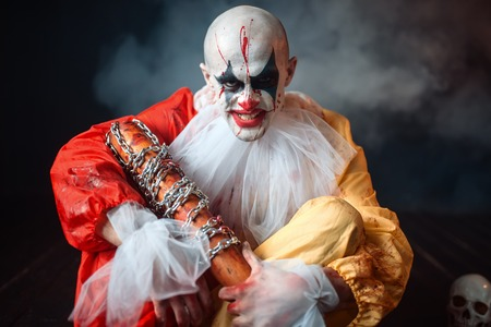 Scary bloody clown, scattered parts of human body