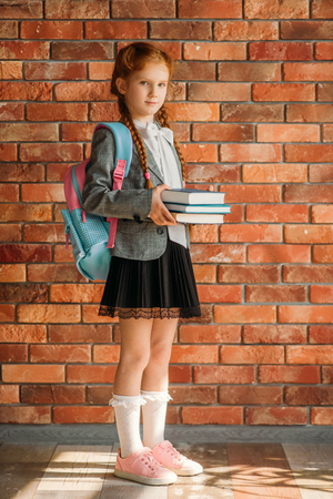 Cute schoolgirl with schoolbag holds textbooks