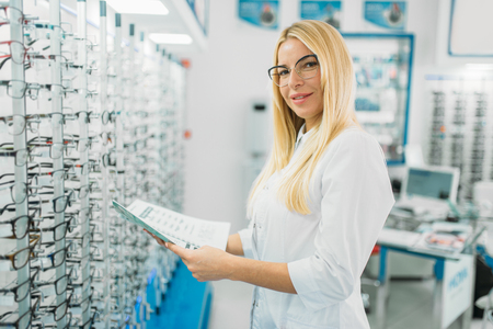 Female optician with glasses catalog in hands Stok Fotoğraf