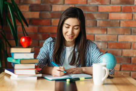 Female student sitting at the table with textbooks Stok Fotoğraf