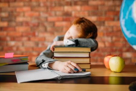 Tired female pupil asleep on stack of textbooks Reklamní fotografie