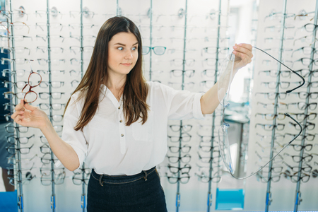 Surprised lady holds huge glasses in optic store Фото со стока - 121627870