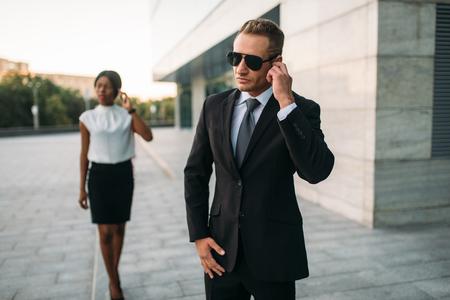Garde du corps en lunettes de soleil et femme d'affaires noire Banque d'images