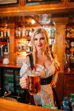 Sexy waitress held out a mug of fresh foamy beer