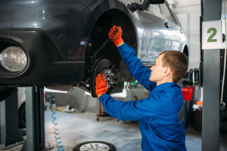 Mechanic with wrench repairs the suspension of car Banco de Imagens