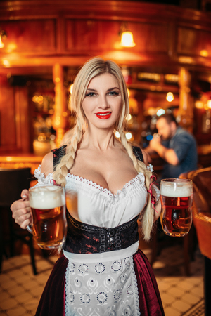 Sexy waitress holds two mugs of fresh beer in pub 免版税图像