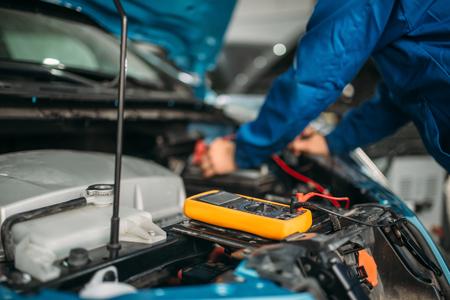Car electrician checks the battery level Imagens