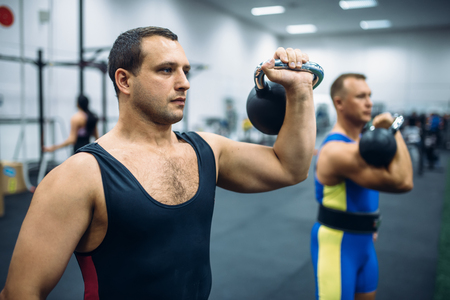 Athletes with weights in gym, kettlebell lifting Stock Photo