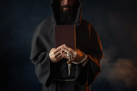 Medieval monk holds book and wooden cross in hands