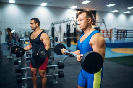Strong male athletes works with weights in gym 写真素材