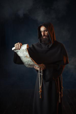 Le moine médiéval lit une prière dans le manuscrit antique Banque d'images