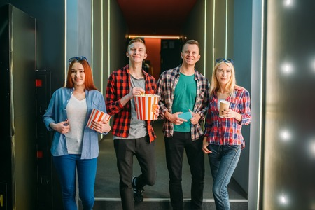 Teenagers with popcorn poses in cinema hall