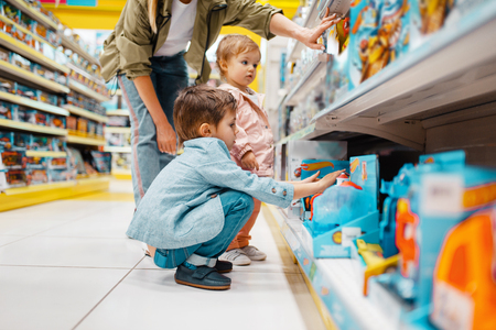 Mother with her children at the shelf in store Stock Photo