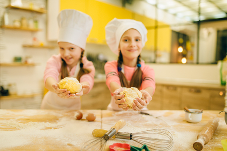 Two little girls cooks in caps shows dough balls