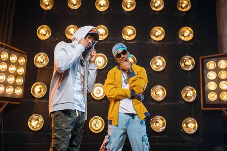 Two black rappers in caps on stage with spotlights Stock Photo