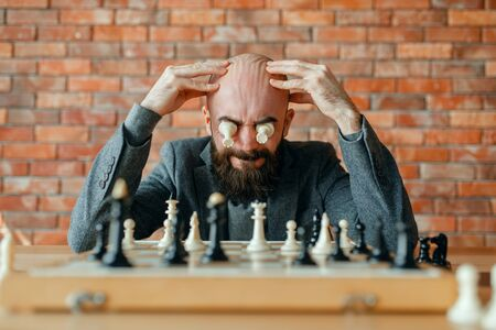 Male chess player with figures in the eyes Imagens