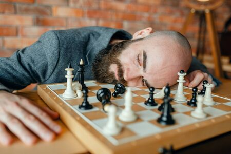 Tired male chess player sleeping on the board