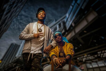 Two black rappers poses on night city street