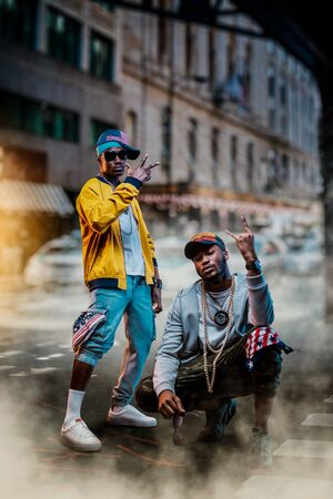 Black rappers in caps, city street on background