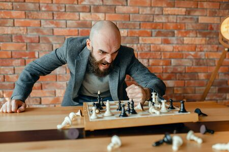 Angry chess player beats his fist on the board