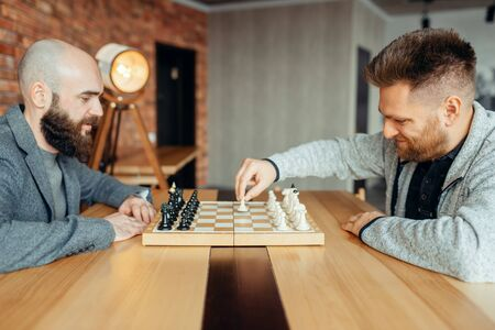 Male chess players begin playing, the first move