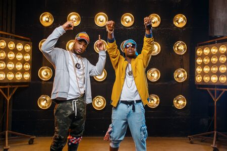 Two black rappers in caps, perfomance on stage Stock Photo