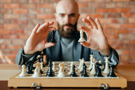 Male chess player holds white and black figures